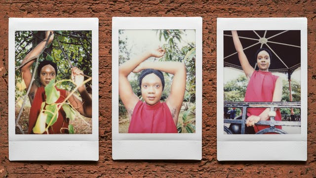 Photograph of three Instax Mini instant film prints in a line, resting on a textured brick surface. All three prints show the same woman. The print on the left shows her nestled within the branches and leaves of tree with her right arm raised up up to show her armpit hair. The print in the centre shows her from the chest up with both her arms raised over her head revealing her armpit hair. Behind her is the green leaves of shrubs and trees. The print on the right shows the same woman standing outside under a large bandstand structure. Her right arm is raised up into the air to show her armpit hair.