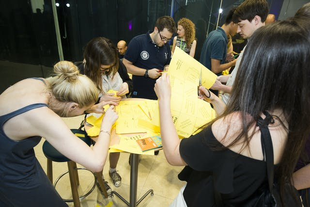 Photograph of a group of people standing at tall tables cutting and folding yellow sheets of paper that cover the surface of the tables.