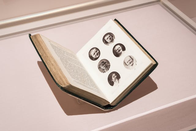 Photograph of a glass exhibition display case showing an open printed book, held in a book cradle. The open double page spread shows text on the left page and 6 circular portraits of people