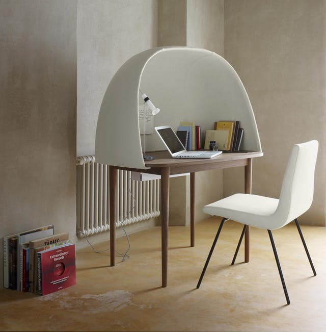 Colour photograph of a walnut wood desk with a white curved shield surrounding it on three sides.