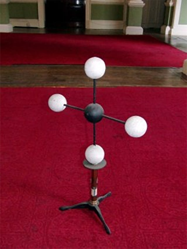 A molecular model in the shape of a cross, with a black ball at the centre, connected to four white balls.