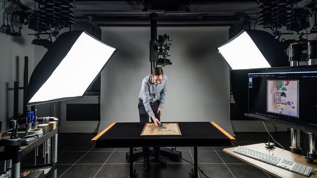 Photograph of a windowless photographic studio. In the centre is a table covered in a black cloth. Standing over the table is a man holding a light meter above an artwork which is resting on the table. Behind him is a large camera stand. To either side are large softboxes mounted on studio flash heads. In the foreground to the left is a trolley containing studio accessories. In the foreground to right is a computer display and keyboard.