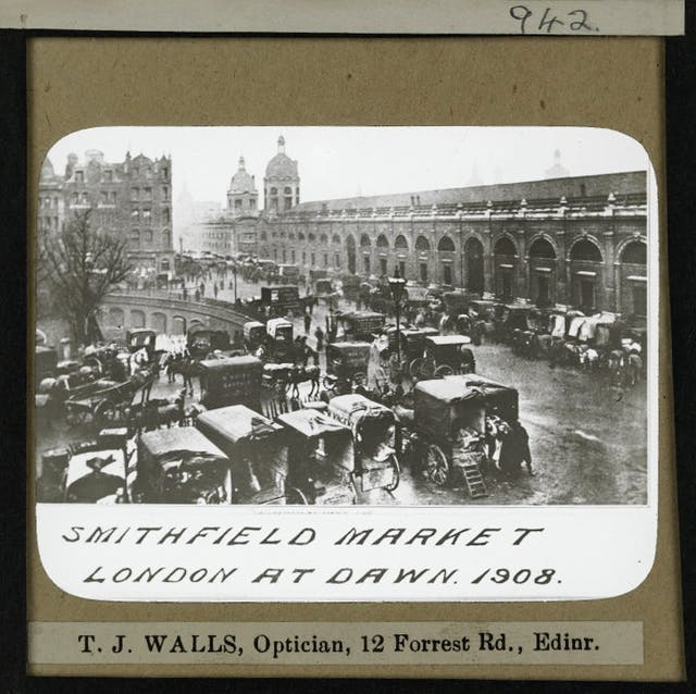 Photograph of a glass slide with a handwritten caption. The slide itself shows a black and white photograph of a brick market building with many horses and carriages in the foreground.