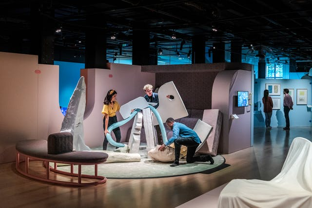 Photograph of an exhibition space showing 3 people working together with large irregular shaped objects to create a sculpture. In the background two other people are exploring other areas of the exhibition.