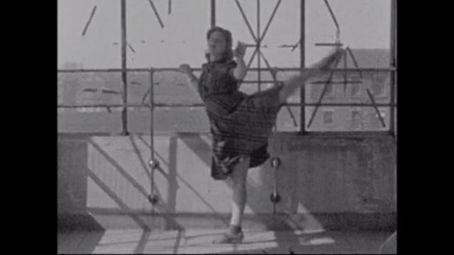 Pregnant women with their leg up in a ballet pose, while holding a side railing.