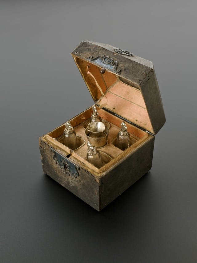 Photograph of small old case, opened to reveal five perfume bottles inside. Ornate clasp.