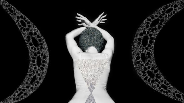 Artwork made up of a black and white photograph of a female figure from behind, from the waist up, against a black background. Her arms are held above her head and her wrists cross, fingers extended. Embroidered into the photographic print with grey thread is a crisscross floral pattern which exactly covers her head and hair. Across her back, embroidered in silver thread is a large triangle connected to a smaller triangle. Either side of the figure are two large curved forms made up of a layered texture of dots.