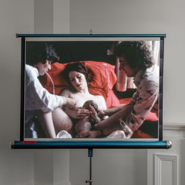 Photograph of an old retractable cine film projector screen and stand, in the corner of a white walled room. To the right of the screen can be seen the reveals of a window with marble-like window sill and moulded wooden panels. On the screen is projected an archive colour film of a woman having just given birth, lying on red bedsheets and pillows. On her left is a man reaching over to hold the baby. To her right is a woman with a tube held in her mouth clearing the baby