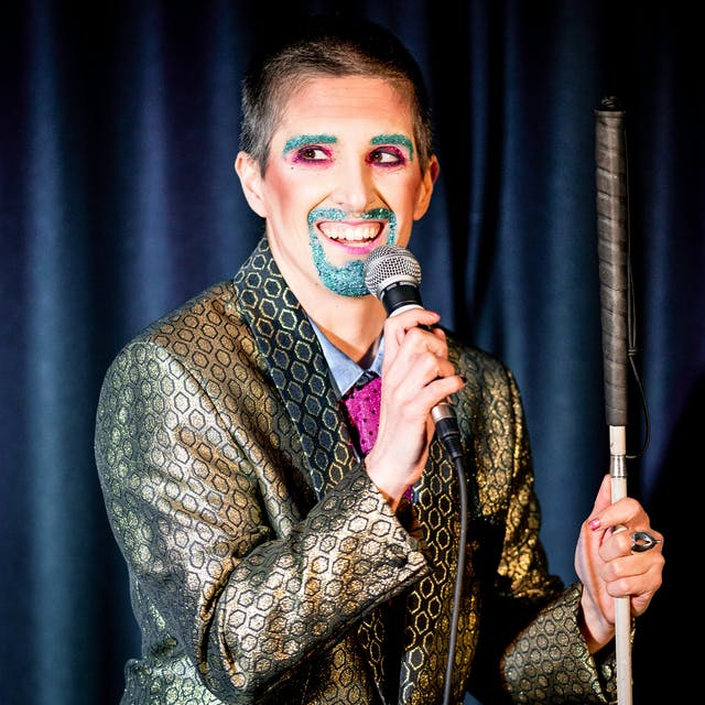 Photograph showing a performer on a stage in a small theatre. The performer is dressed in a shiny gold suit. Their right hand is holding a microphone to their mouth. In their left hand they are holding a white cane. Their mouth and eye brows are covered in blue glitter make-up