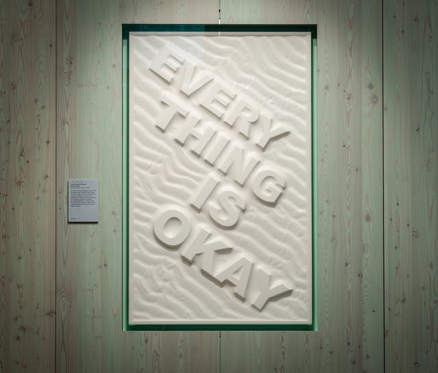 A photograph of a large off-white rectangular panel with EVERY THING IS OKAY in relief in large capital letters diagonally across the panel from left to right with one word on each diagonal line. Repeating undulating patterns also move across the panel in the same direction, and the text appears as though a relief in sand. The panel is hung on a light green wood panelled wall.