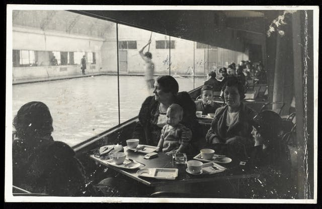 Reproduction of a black-and-white photograph showing a group of women and children at a table having tea watching while people are in the swimming pool at the Pioneer Health Centre