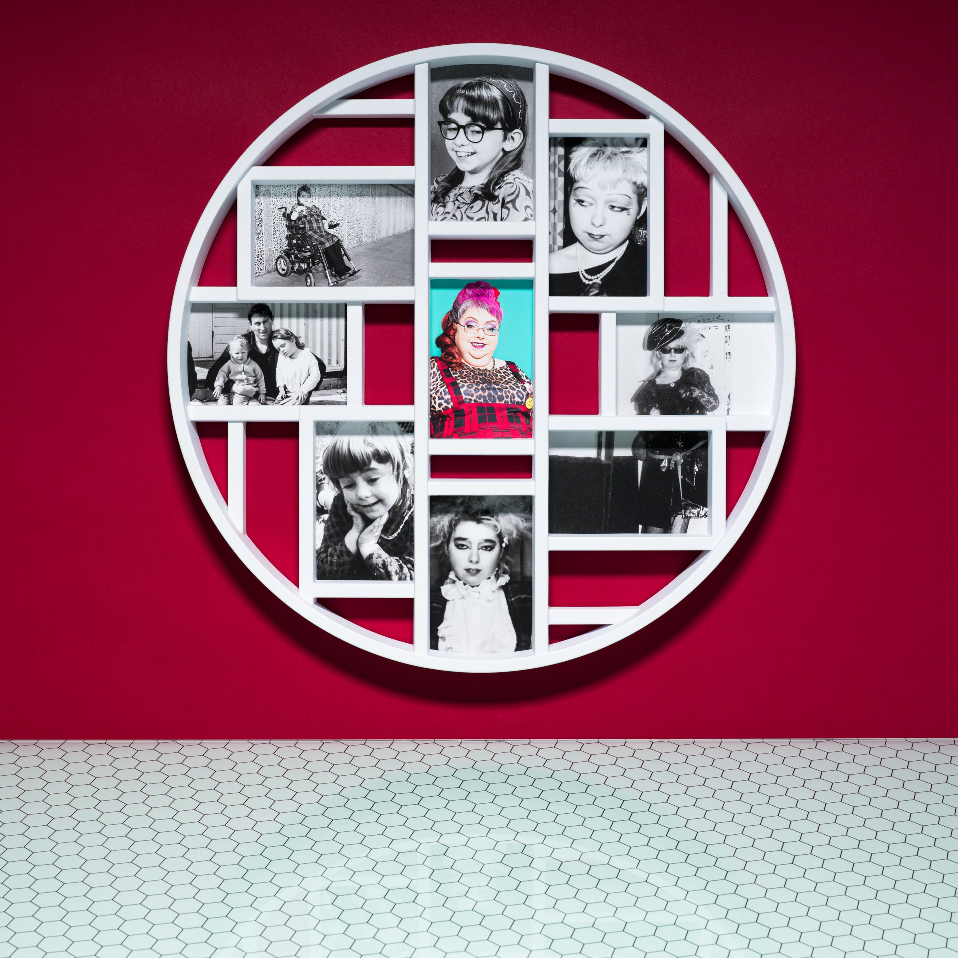 Photograph of a multiframe photo frame containing nine photographs, one in colour and eight in black and white. The frame is hung on a crimson wall above a glass patterned tabletop.