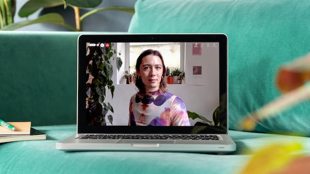 """Photograph of a laptop sitting on a green sofa next to a notepad and pen. On the laptop screen is a live event showing Es Morgan. They have shoulder-length brown hair are wearing a purple, white, and red patterned top. Behind them is a window ledge displaying small cacti and succulents in pots. In the top left-hand corner of the screen is a red telephone icon with other video call icons """"People"""" and """"chat""""."""