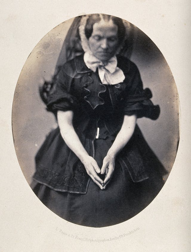 Photograph of a woman, seated, wearing a black dress and veil