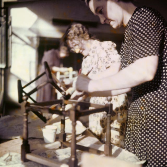 Photograph from the mid-20th Century Peckham Pioneer Centre, showing three women who appear to be assembling and staining some sort of wooden furniture, possibly the bottom of a chair.