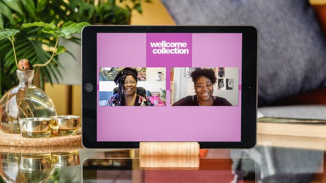 Photograph of a tablet in a stand on a glass coffee table with plants and a sofa behind it. On the tablet screen is a live online event of Cheryl Martin and Rianna Walcott in conversation. The words Wellcome Collection are at the top centre of the screen.