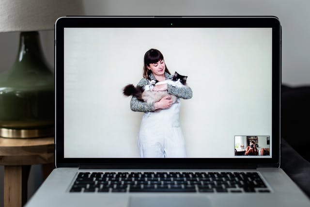 Photograph of an open laptop within a domestic scene. Most of the image is taken up with the screen, with part of the keyboard and trackpad visible. On the screen is a video call showing a woman standing against a white wall looking down at a cat she is holding in her arms. In the bottom right corner of the screen the photographer can be seen in a small floating window, camera to her eye, in the process of taking the picture.