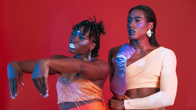 Two artist performers posing in luminous make-up and clothes against a red background.