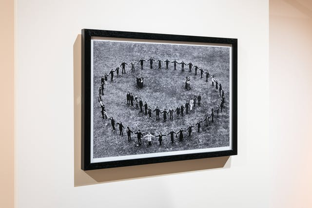 Photograph of an exhibition gallery showing a framed print hung on a cream coloured wall. The frame is black and mounted inside is a black and white photograph showing an aerial view of people on the ground holding hands and forming a circle, within which are clusters of people representing two eyes and a mouth. Together they all make a large smilie face.