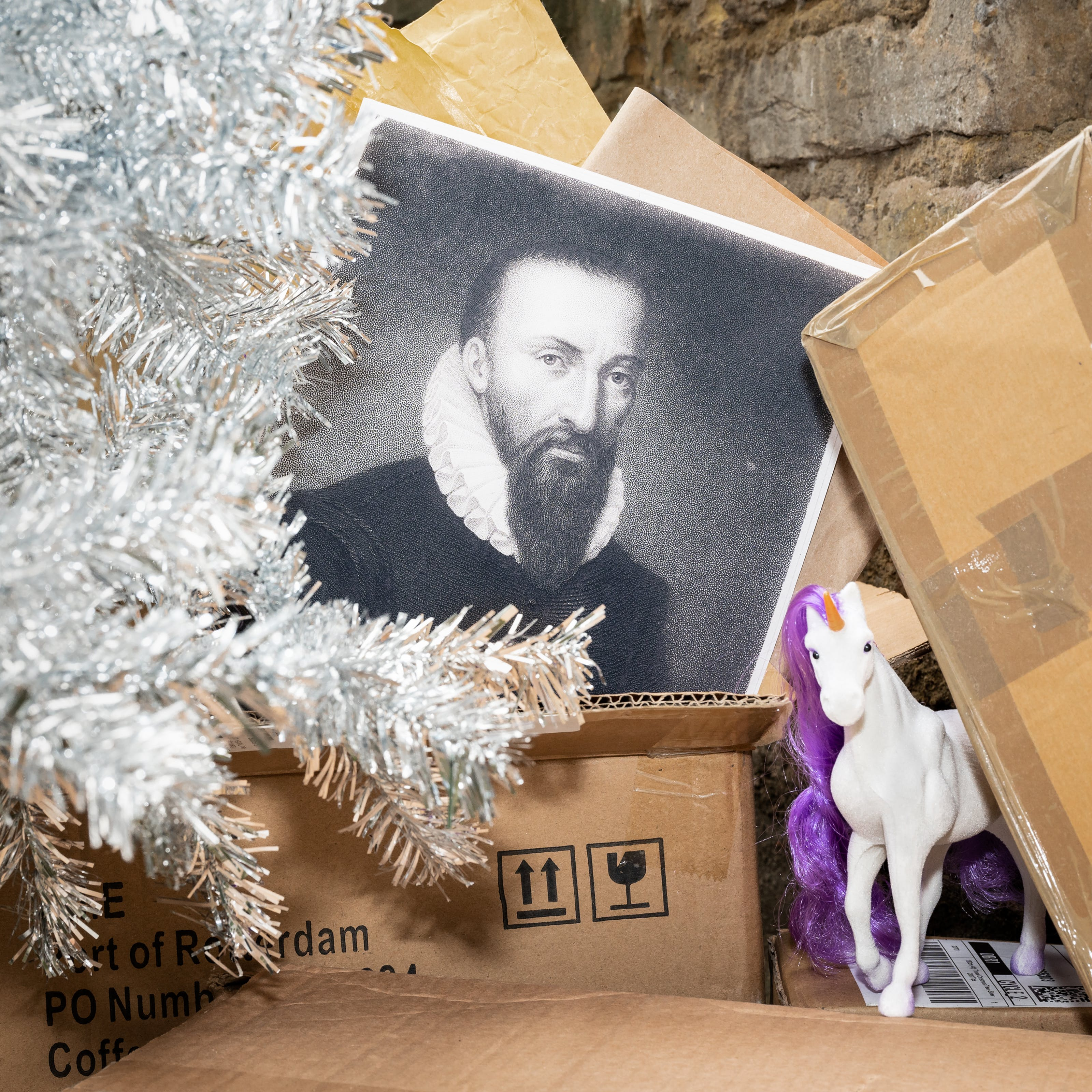 Photograph of a pile of brown cardboard boxes quite closeup. Next to the boxes on the left is part of a silver tinselled Christmas tree, bare of decorations. Sticking out of one of the cardboard boxes is a balck and white print of a bearded mad with a ruff from the 16th century. One the right hand side, appearing from behind a box is a white plastic unicorn figurine with an orange horn and a purple mane.