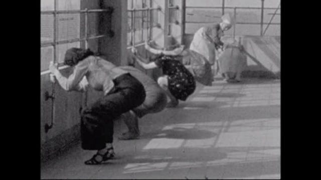 Black and white image of women in a row bending down while holding railing at the side of a room