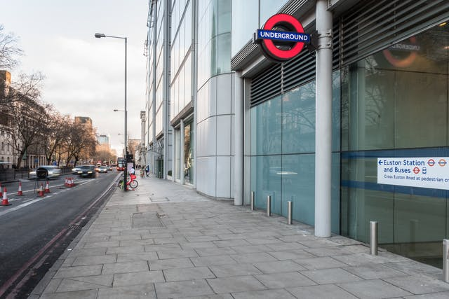 A photograph showing Euston Square underground station on Euston Road at street level with the Wellcome Trust building beyond it, and the Wellcome Collection building beyond that. A pavement runs along all three without the interruption of roads.