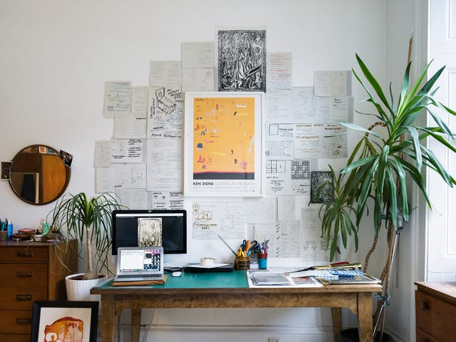 Photograph of a wall covered in pieces of paper which contain sketches and drawings. In front of the wall is a desk on which is a computer screen and laptop, a cutting mat and pen pot holders. Tot he right of the desk is a large pot plant and to the left is a chest of drawers.
