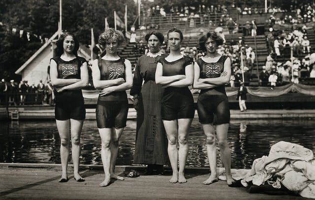 Black and white photo of five women standing in a line in front of a pool. Four of them wear old-fashioned swimming costumes. The other one wears a long dress.