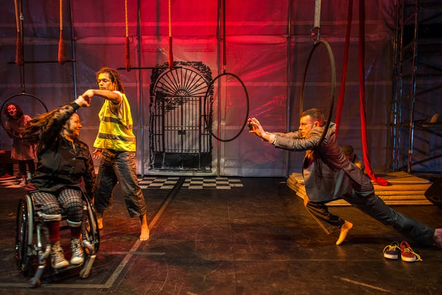 Photograph of a theatre stage with several performers. Stage left two performers, one standing and one seated in a wheelchair, perform a dance-like-manoeuvre where one twirls under the arm of the other. To the right of the frame a third performer is reaching towards the others through a large metal ring, as if his movements are restricted by the prop.  The stage is lit in a deep red hue.