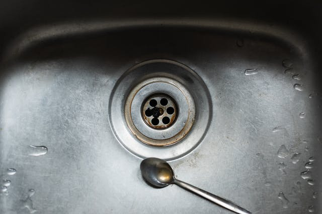 Photograph of a stainless steel kitchen sink, so close up that the sink fills the frame. In the centre is the plug hole with brown stains and a dark round squashed object. Next to the plughole is a teaspoon with a puddle of brown water in it. All over the surface of the sink are small patches of water.