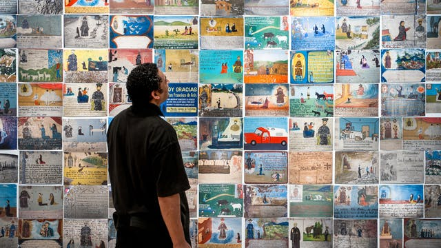 Photograph of an exhibition gallery wall covered in colourful Mexican votive plaques, depicting many and varied scenes. In front of the wall, stood in partial silhouette is a man, side on, look up at the votives.