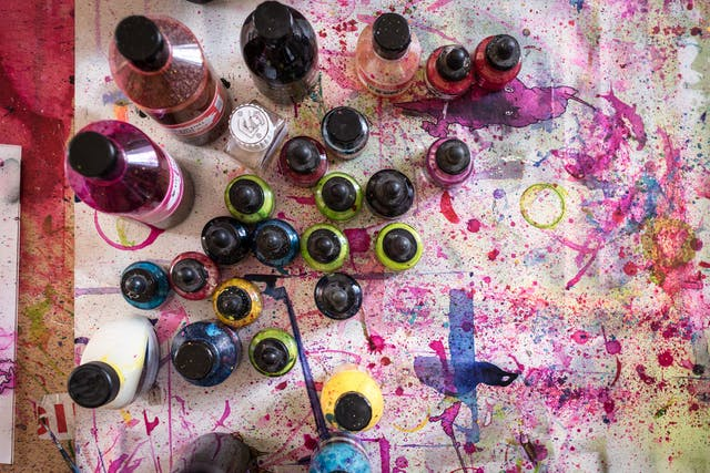 Photograph from above of colourful inks on a paint spattered drawing board.