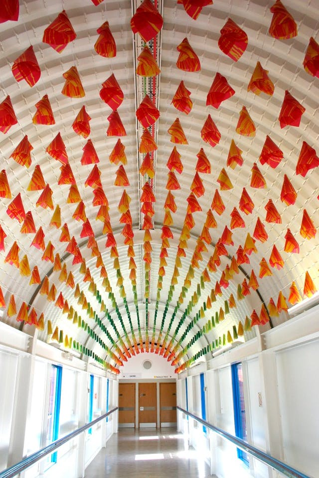 Individual red, green and yellow plastic cones hang from the ceiling in a hospital corridor.