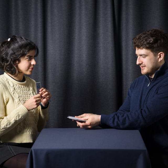 Photograph of a young man and woman performing magic tricks with a deck of playing cards, in front of a grey curtain.