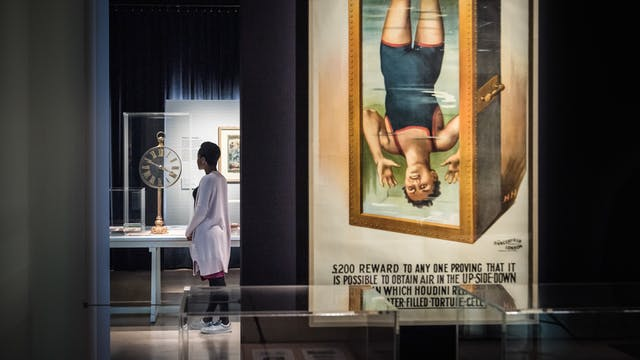 Photograph of a visitor exploring the exhibition, Smoke and Mirrors at Wellcome Collection. Photograph shows a women in the background looking at an object in a display case. In the foreground is a large colourful poster showing a man in a Victorian swimming costume suspended upside down in a tank of water.