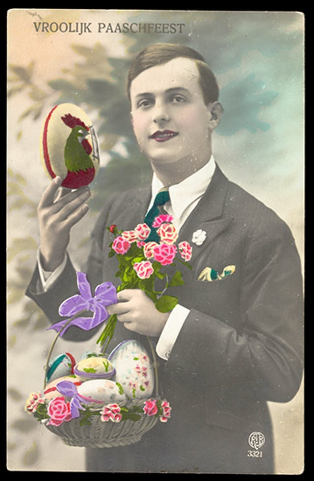 A young man in a smart suit holds an Easter egg with an image of a cockeral on it in one hand and a basket of decorated Easter eggs and a bunch of brightly coloured flowers in the other hand.