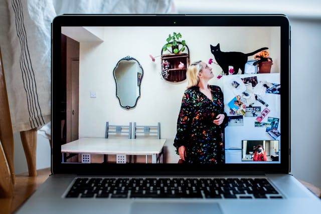 Photograph of an open laptop within a domestic scene. Most of the image is taken up with the screen, with part of the keyboard and trackpad visible. On the screen is a video call showing a woman standing in a kitchen setting, next to a fridge freezer. She is looking up to the top of the fridge where a black cat is standing looking towards the camera. In the bottom right corner of the screen the photographer can be seen in a small floating window, camera to her eye, in the process of taking the picture.