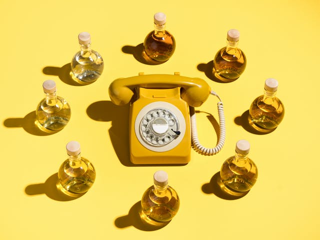 Photograph of a yellow rotary dial telephone surrounded in a circle by 8 specimen bottle containing a yellow liquid which get lighter in hue as you travel clockwise around the circle. The whole scene has been photographed against a bright solid yellow background.