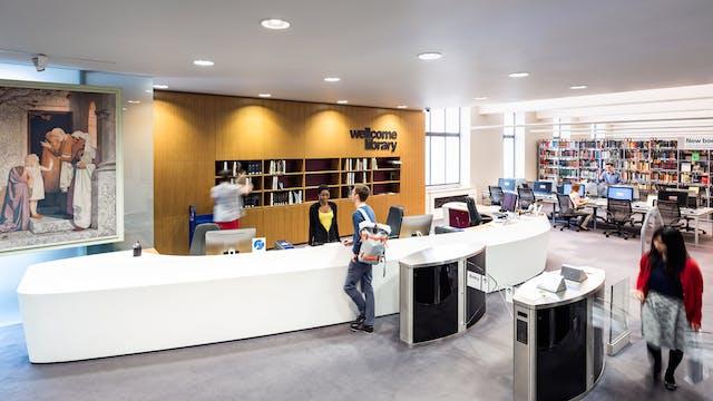 入口的照片对图书馆的入口。在中心是一个大曲线形状的大白信息台。右边是一位女士在退出过程中的安全障碍。一个女人站在信息台后面与戴着背包的图书馆访客谈话。在桌子后面有人在货架上将书籍放在架子上,有一个大的标志,惠康图书馆。在右边的距离,可以看到图书馆的货架和访客。左边是一部大型油画的一部分,挂在磨砂玻璃墙上。