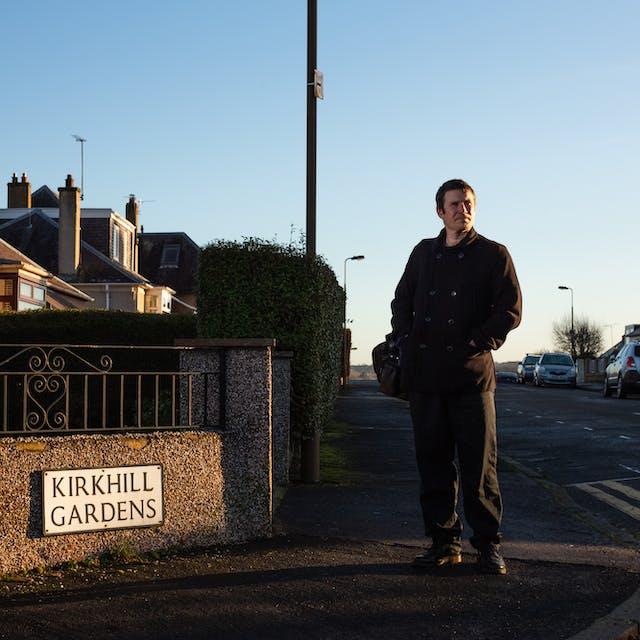 照片中一名男子穿着黑色外套和裤子,右肩挎着一个包。他站在一个街角,面对着镜头,但却看着右边的远处。一束低金色的阳光把他从周围的郊区街景中认出来,这些街景由停放的汽车、房屋和街灯组成。天空是纯蓝色的。在左边的墙上有一个路名牌,上面写着: