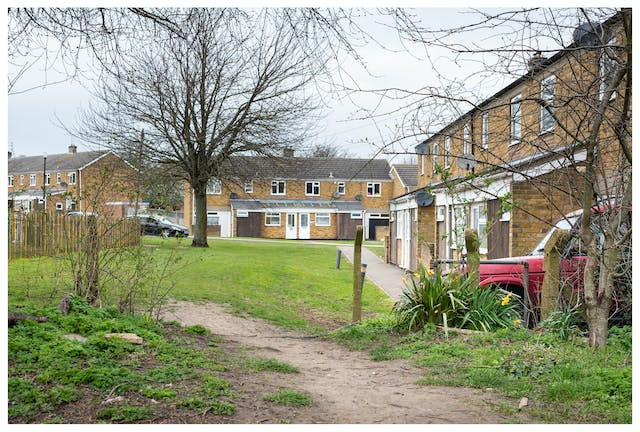 Photograph of a rough pathway leading to a housing estate. The houses are yellow brick and built around a communal green. The pathway is a well worn and cuts though a broken down fence, to the right of which is a small bunch of bright yellow daffodils. Behind the flowers is a red off-road vehicle.
