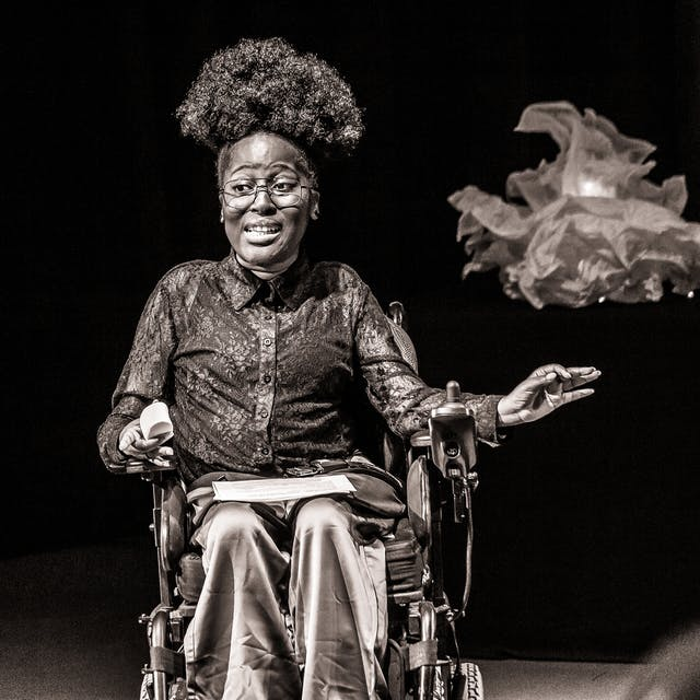 Black and white photograph with a warm tone. The image shows a young woman seated in a wheelchair against a black curtain and lit by a spotlight. She is performing to an audience. She has been captured