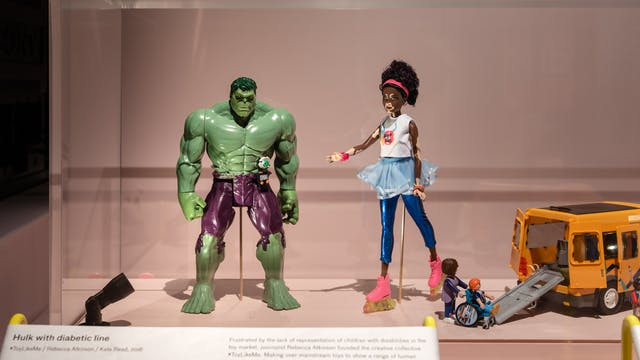 Photograph of an exhibition display case showing from left to right, an Incredible Hulk toy with a diabetic medication line attached, a Barbie doll with vitiligo and a Playmobile vehicle with extended rear access ramp and a child in a wheelchair.