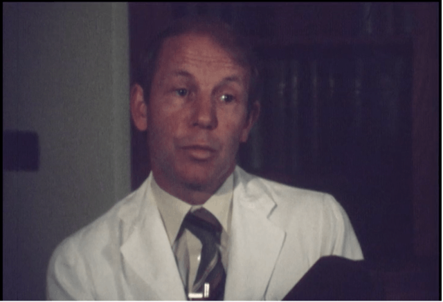 Film still of a man wearing a tie and white doctor