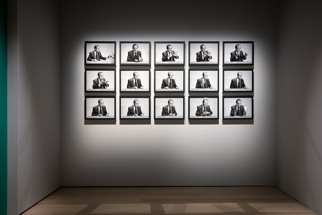 Photograph of a series of 15 framed black and white photographs which show a man performing