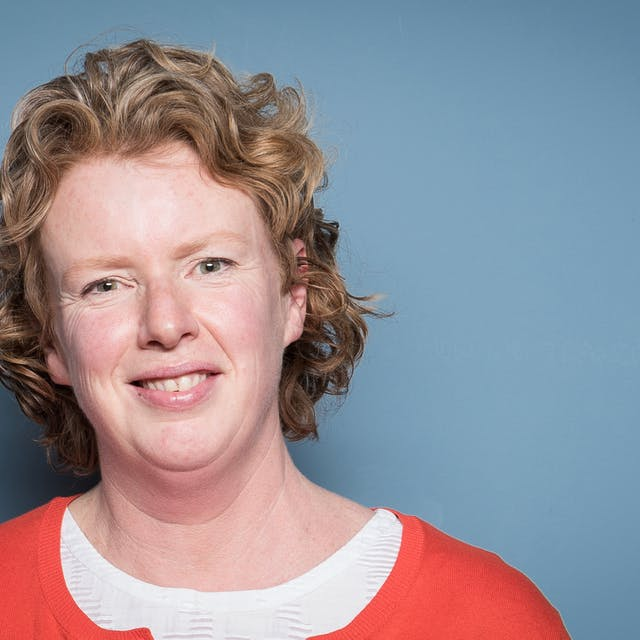 Photographic head and shoulders portrait of Suzanne O'Sullivan against a blue wall.