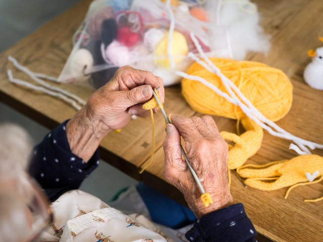 A photograph of the hands of an elderly woman knitting. They are holding two grey knitting needles and are making stitches with yellow wool. In the background is a ball of yellow wool and a bag containing small balls of wool in various colours.