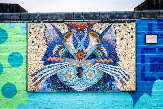 Photograph showing a brightly coloured abstract ceramic mosaic of a cat, in the style of Louis Wain. The mosaic is hung on a low brick wall which is also brightly coloured. Above the wall, a thin slither of sky can be seen. To the right side is an information plaque.