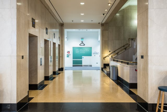 A photograph of the first floor facing four lifts on the left, a staircase going downwards and upwards on the right, and a cloakroom directly opposite  had you come straight in with from Euston Road with the entrance behind you.