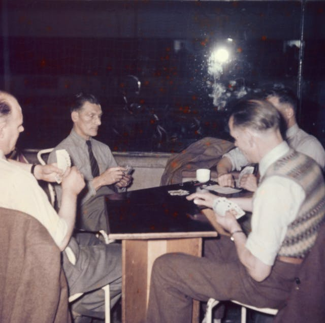 Photograph from the mid-20th Century Peckham Pioneer Centre, showing four men seated at a table with playing cards in their hands.